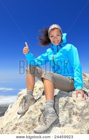Hiker woman at mountain top summit enjoying view giving success thumbs up sign smiling happy of her hiking achievement. Beautiful happy smiling female hiker on the top of volcano Teide, Tenerife Spain
