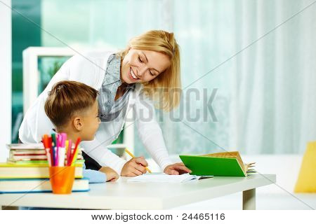 Portrait of smart tutor with pencil correcting mistakes in pupil?s notebook