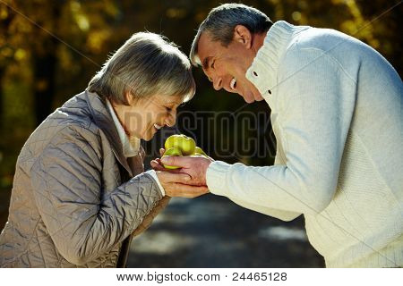 Photo of aged woman smelling apples in her husband hands in the park