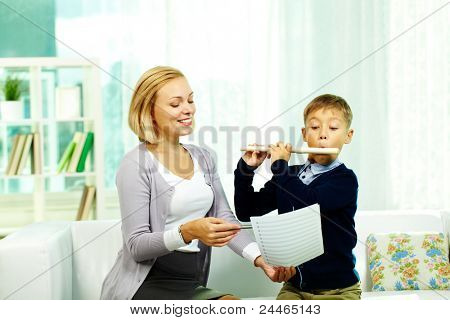 Portrait of pupil playing the flute while looking at notes in tutor?s hand
