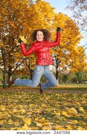 Chica de la chaqueta roja salta en el Parque