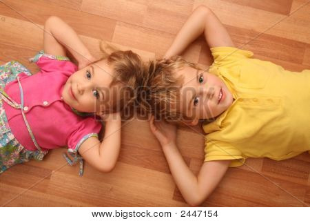 Brother And Sister Lie On Floor