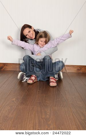 Young Mother And Daughter Sitting On Floor At Home