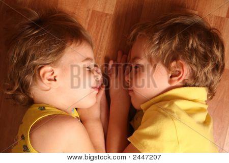 Two Children (Girl And Boy) Sleep On The Floor
