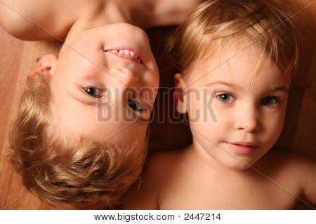 Two Children Lie On Floor