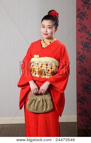 Mujer oriental en Kimono japonés tradicional rojo