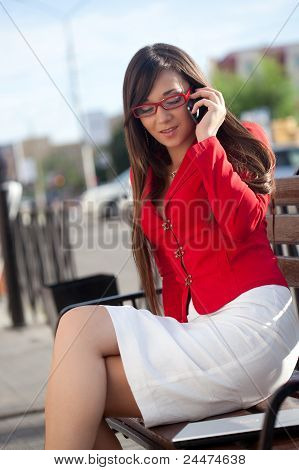 businesswoman calling by phone, wearing red jacket