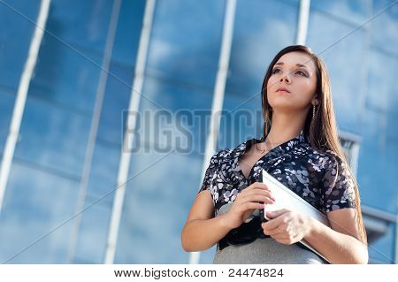 woman holding laptop over glass building