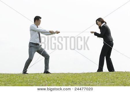 Business Couple Playing Tug Of War