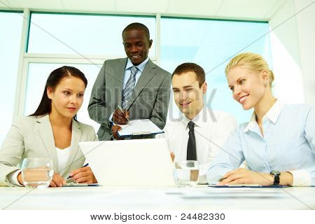 Four businesspeople sitting at table, watching presentation and making notes