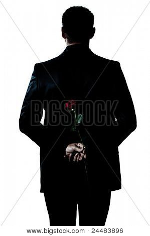 one caucasian backside man holding a rose flower portrait silhouette in studio isolated white background