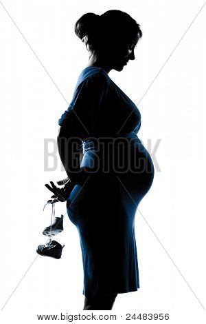 beautiful caucasian pregnant woman holding baby shoes in silhouette on studio isolated white background