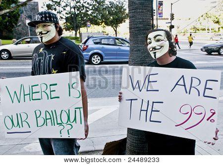 Zwei Demonstranten in Masken halten Sie Zeichen in L.A. zu besetzen