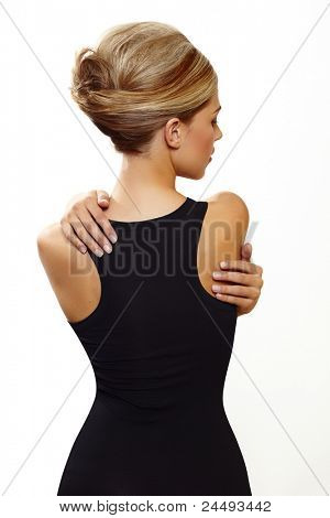 pelo con mujer hermosa en francés rollo updo en sexy vestido negro de pie con su espalda contra