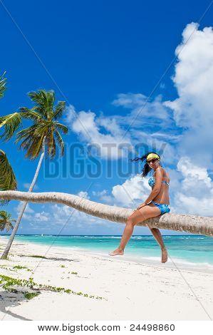 Gebräunte Frau sitzt auf einem Palm White Sand Strand
