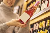 Closeup Of Young Girl Choosing Champagne Or Wine At Supermarket. Cheerful Woman Holding Wine Bottle  poster
