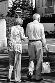 Photo Back View Of Well-dressed Silver-haired Senior Couple Aged Man And Woman Walking Arm-in-arm In poster