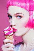 Trendy girl with pink hair wearing headphones is eating ice cream. Pink background. Youth style, lei poster
