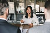Business, career and placement concept - young asian woman smiling and holding resume, while sitting poster