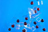 Martini Glass With Ice Cubes And Cherries On A Bright Blue Background With Copy Space. Refreshing Co poster
