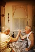 stock photo of old couple  - Old couple arm wrestling in a vintage ambiance