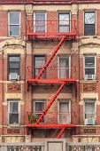 Traditional Red Fire Escape Of An Apartment Building In New York City. poster