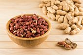 Wooden Bowl Full Of Peeled Peanuts And Peanuts In Nutshell On A Wooden Table poster
