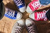Red, Blue And Gray Sneakers Standing In The Circle On Dry Sand, View From Above. Friendship, Fashion poster