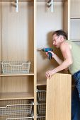 picture of assemblage  - The man is engaged in repair and furniture assemblage - JPG