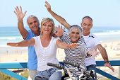 stock photo of foursome  - happy foursome gone for a ride by oceanfront - JPG