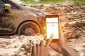 Man Hand Using Smartphone Calling Emergency For Help Car Tire Stuck In The Mud Background. Car Wheel poster