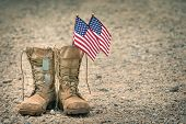 Old Military Combat Boots With Dog Tags And Two Small American Flags. Rocky Gravel Background With C poster