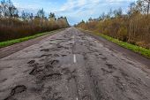 Dangerous Potholes In The Asphalt Rural Road. Road Damage. poster