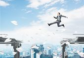 Businessman Jumping Over Gap With Flying Paper Planes In Concrete Bridge As Symbol Of Overcoming Cha poster
