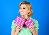 Happy Woman In Pin-up Style Dress Holding Gift Box. Beautiful Blonde Pin-up Girl Holds Gifts Boxes.  poster