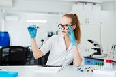 Scientist Analyzing Microscope Slide At Laboratory. Female Working In Laboratory With Microscope. Re poster
