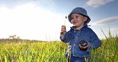 stock photo of little boy  - There is a nice little boy walking on the summer meadow - JPG
