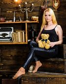 Girl In Black Clothes Holds Teddy Bear Toy In Hand, Wooden Interior On Background. Lady Blonde Enjoy poster