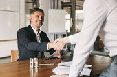 Business, career and placement concept - satisfied director man 30s smiling and shaking hands with m poster