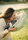 Mothers Love. Mother Woman Kiss Baby Son In Basket On Natural Landscape poster