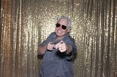 Man Posing in a Photo Booth. A handsome man poses and smiles while in a photo booth at a party or we poster