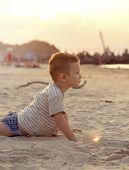 Happy boy playing on the beach near the sea at the summertime. Boy lying on the sand poster