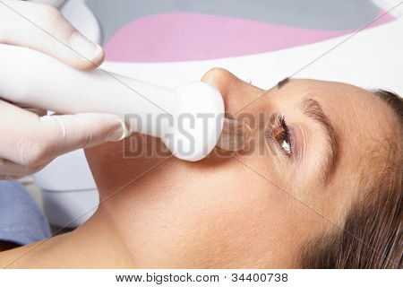 Elderly woman getting high frequency skin treatment in spa
