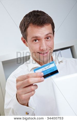 Smiling business man with laptop and credit card in office