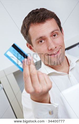 Business man on laptop showing credit card in his office