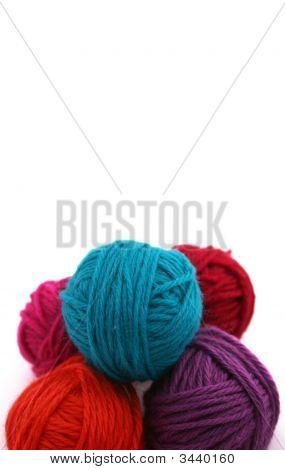 Bolas de hilo de colores brillantes sobre fondo blanco