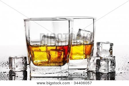 two glasses of scotch whiskey and ice on table isolated on white