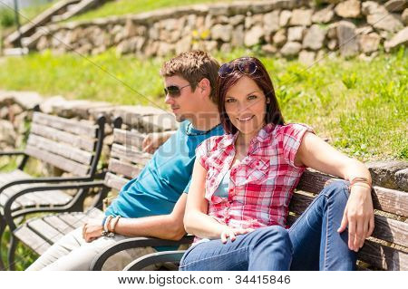 Young couple sitting on bench in park resting happy smiling