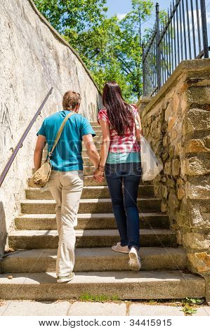 Young couple climbing up city stairs holding hands leisure time