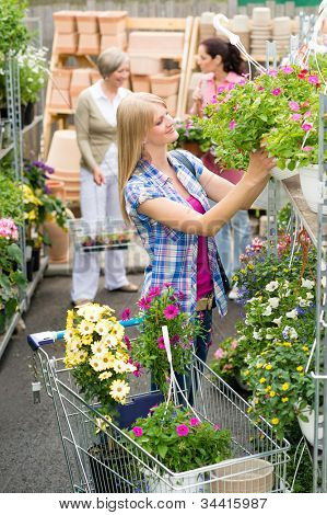 Woman shopping for flowers in garden centre plants selection
